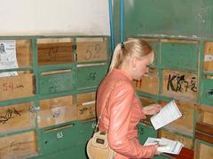 Ольга Вайцберг раскладывает свои листовки по ящикам